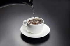 Boiled water is poured into a white cup with black coffee Stock Image