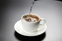 Boiled water is poured into a white cup with black coffee Royalty Free Stock Photos