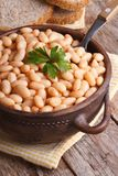 Boiled white kidney beans in a brown pot and bread, closeup Royalty Free Stock Photography