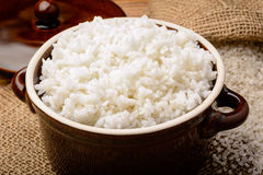 Boiled white rice in ceramic pot on wooden background. Stock Image