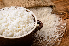 Boiled white rice in ceramic pot on wooden background. Stock Photos