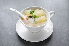 Boiled winter melon soup with chicken rib in white bowl on table royalty free stock image