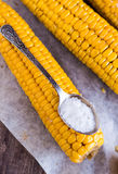 Boiled yellow corn and a teaspoon of salt, close up Stock Photos