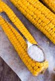 Boiled yellow corn and a teaspoon of salt, close up Stock Photos