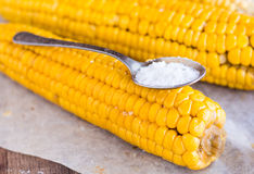 Boiled yellow corn and a teaspoon of salt, close up Royalty Free Stock Photography