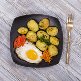 Boiled young potatoes with fried eggs, carrot and tomato. Close up Stock Photos