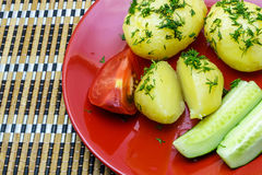 Boiled young potatoes with slices of cucumber and tomato on a plate. Boiled young potatoes with slices of cucumber and tomato on a red plate royalty free stock photos