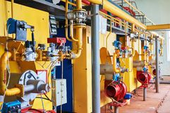 Boiler room with four large yellow cauldrons and red-blue burners. stock photo