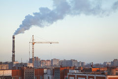 Boiler pipe smoke above roofs of high-rise apartment buildings Stock Photo