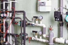 Boiler and pipes of the heating system of a house. Water and gas home control station, two white and one brown boiler stock photo