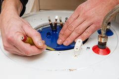 Water heater repairment open tub close up. Boiler repair with master hands with screwdriver stock photo
