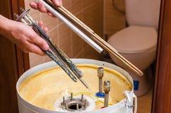 Boiler repair, replacement of broken water heating element.  royalty free stock images