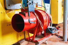 Boiler room with four large yellow cauldrons and red-blue burners. stock photography