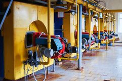 Boiler room with four large yellow cauldrons and red-blue burners. Boiler with four large boilers yellow and red and blue burners stock photo