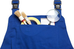Boiler Suit Concept, Searching for a Handy Man, magnifying glass. And Paint brushes Royalty Free Stock Photography