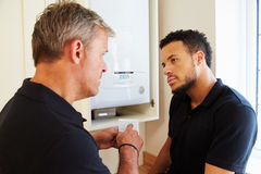 Boiler technician and apprentice servicing domestic boiler Royalty Free Stock Photography