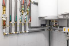 Boiler for water heating, piping system. Technical room for water heating with white boiler and piping system with green and red valves Royalty Free Stock Image