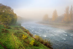 Boiling autumn river in fog Stock Image