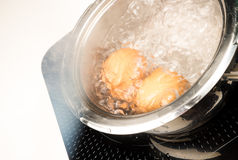Boiling eggs. Preparing hardboiled eggs in a steel pan Royalty Free Stock Photos