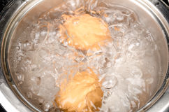 Boiling eggs. Preparing hardboiled eggs in a steel pan Stock Image