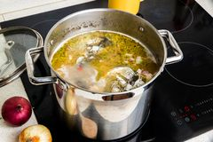 Boiling fish soup in pot. Pot with boiling fish soup on hot ceramic hob stock photography
