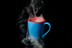 Boiling Hot Coffee in Blue Cup on black background Royalty Free Stock Image
