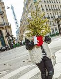 Trendy child in Paris, France hiding behind Christmas tree. Boiling hot trendy winter in Paris. trendy child in Paris, France hiding behind Christmas tree Stock Photo