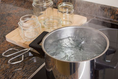 Boiling jars. Boiling glass jars for sterilisation and preparing homemade jam royalty free stock images