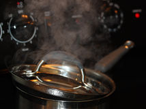 Boiling Pot. Steam coming out of boiling pot on the hot stove Stock Image