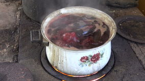 Boiling pot with beet vegetable on old  stove stock footage