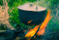 Boiling pot on the campfire on picnic. Cooking in field conditions, boiling pot at the campfire on picnic. Vintage effect with soft focus Stock Photography