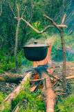 Boiling pot on the campfire on picnic. Cooking in field conditions, boiling pot at the campfire on picnic. Vintage effect with soft focus Stock Image