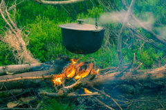Boiling pot on the campfire on picnic. Cooking in field conditions, boiling pot at the campfire on picnic. Vintage effect with soft focus Stock Images