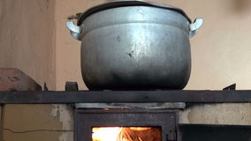 Boiling pot on retro poor fireplace in farm stock video