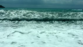 Boiling sea. Giant waves roll to the shore. Sea surf huge waves with white foam splashing around shore. stock video footage