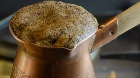 Boiling turkish coffee in copper cezve. Boiling turkish coffee in copper cezve on gas stove close up stock video footage
