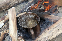 Boiling water. Wood and boiling water in camp fire, camping Stock Photo