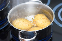 Boiling in water. Fresh potato boiling in water on ceramical stofe Royalty Free Stock Image