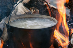 Boiling water in the bowler on the bonfire.  stock photos
