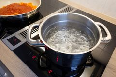 Boiling water in a cooking pot an a pan on a stove. Boiling water in a cooking pot an a pan on a induction stove stock photo