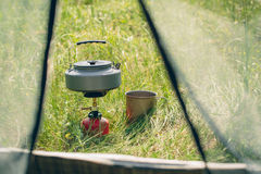 Boiling water in kettle on portable camping stove Stock Photo