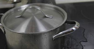 Boiling Water In The Pan that is covered with a lid in the kitchen royalty free stock image