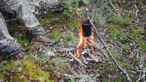 Boiling water in pots above the fire in outdoor stock video footage