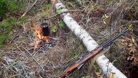 Boiling water in pots above the fire in outdoor. Hunter shotgun stock video footage