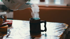 Boiling water is poured into a cup from the kettle stock video
