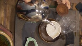 Boiling water pouring into bowl during tea ceremony. Hands holding shiny metallic kettle, pouring hot boiling water into ceramic bowl and covering it with lid stock video