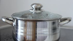 Boiling water in a saucepan with glass lid, closeup. Water gurgles, sprinkles and flows from pan. stock footage