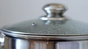 Boiling water in a saucepan with glass lid, closeup. Water gurgles, sprinkles and flows from pan stock video footage