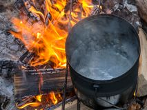Boiling water at the stake. In front of fire stock images