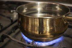 Boiling water in a steel casserole pot in a stove stock photography